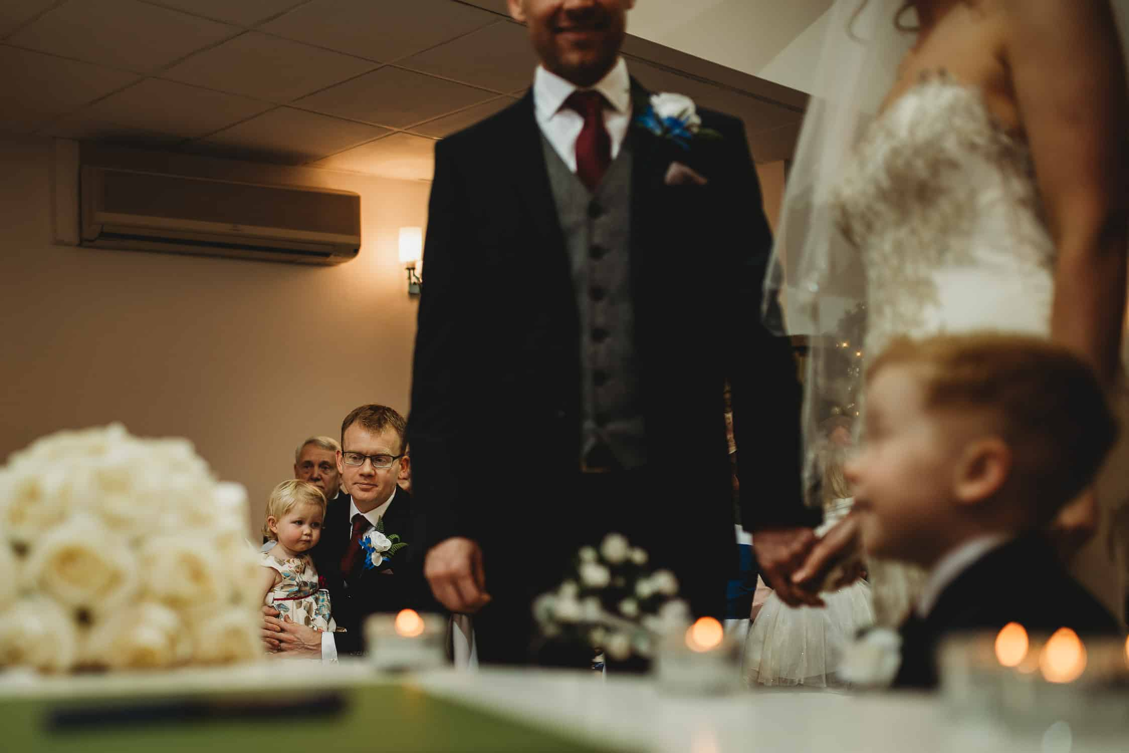 wedding guest holding his daughter during wedding ceremony at Stirk House in Lancashire