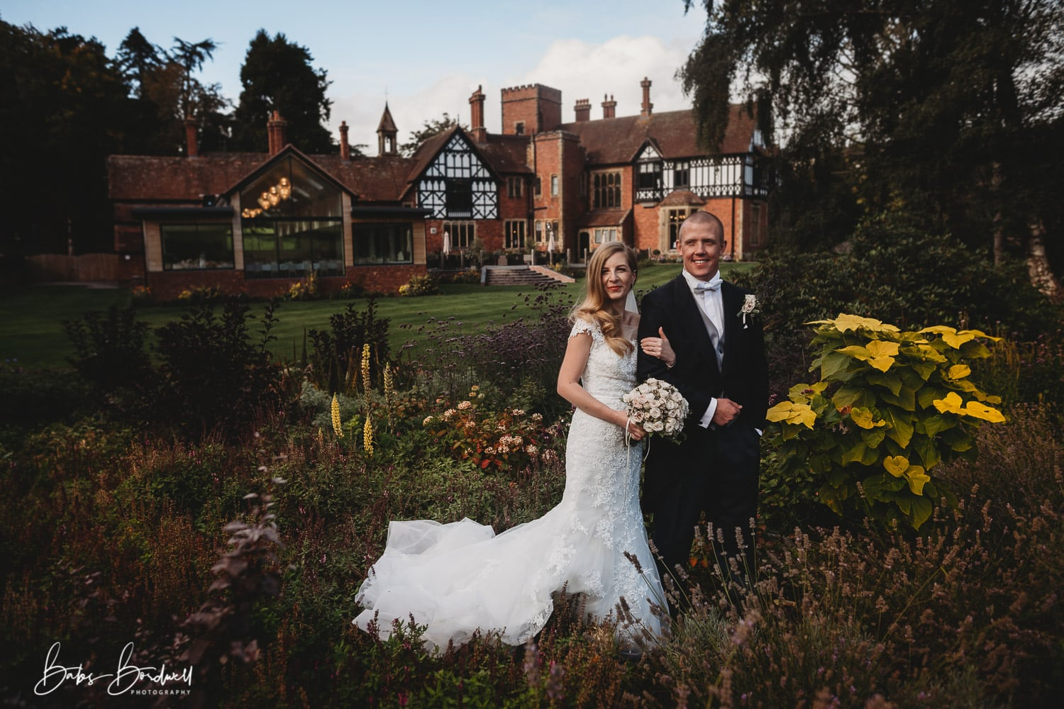 portrait of bride and groom with Tyn Dwr Hall in the background
