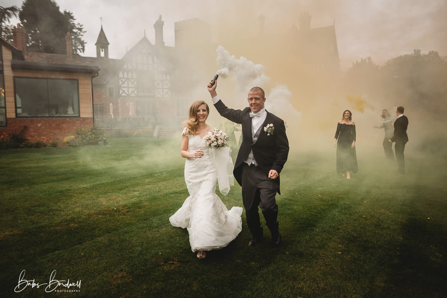 bride and groom running while groom holds a white smoke bomb above his head
